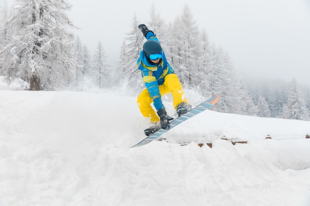 Człowiek z snowboardowe skoki i robienie sztuczek na śniegu