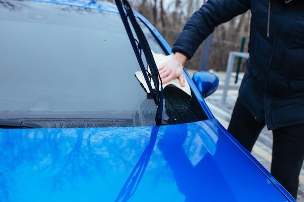 Człowiek z szmatą do wysuszenia samochodu. koncepcja myjni samochodowej