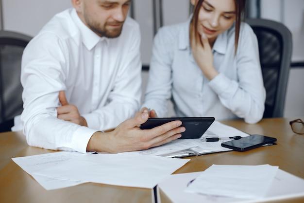 Człowiek z tabletem. partnerzy biznesowi na spotkaniu biznesowym. osoby siedzące przy stole