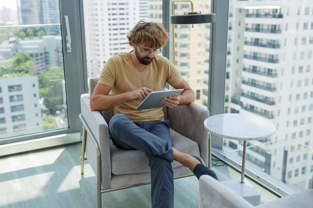 Człowiek z tabletem, siedząc na kanapie w nowoczesnym biurze.