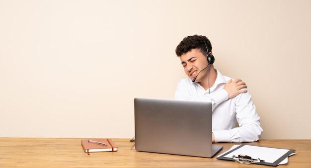 Człowiek z telemarketerem cierpiący na ból ramienia za to, że podjął wysiłek