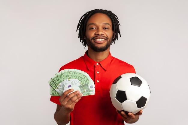 Człowiek z toothy uśmiechem, trzymając piłkę nożną i banknoty euro, patrząc na kamery, obstawiając i wygrywając.