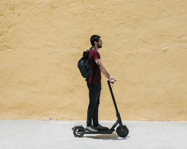 Człowiek z ukosa jedzie na e-skuterze