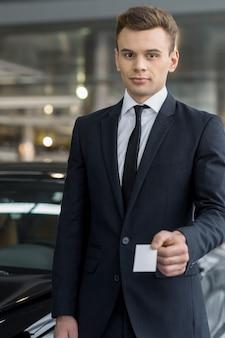 Człowiek z wizytówką. pewny siebie młody sprzedawca klasycznych samochodów stojący w salonie i trzymający kluczyk