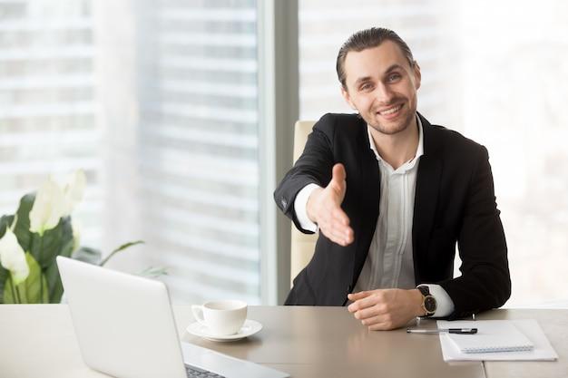 Człowiek z zadowoleniem przyjmuje partnerów biznesowych w negocjacjach