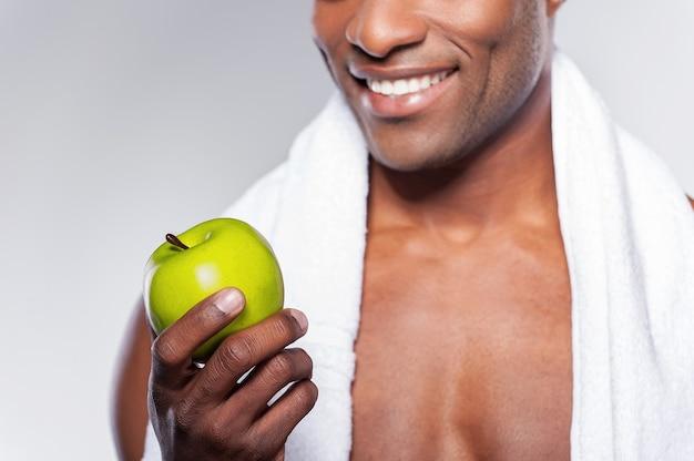 Człowiek z zielonym jabłkiem. przycięty obraz młodego muskularnego afrykańskiego mężczyzny z ręcznikiem na ramieniu, rzucając jabłko i uśmiechając się do kamery, stojąc na szarym tle