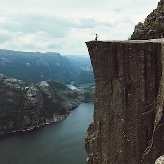 Człowiek z żółtą kurtką stwarza na szczycie skały