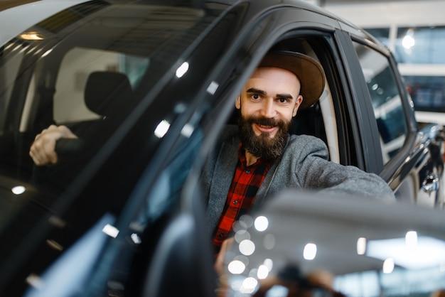 Człowiek za kierownicą pickupa w salonie samochodowym. klient w salonie samochodowym, mężczyzna kupujący transport, firma dealera samochodowego dealer