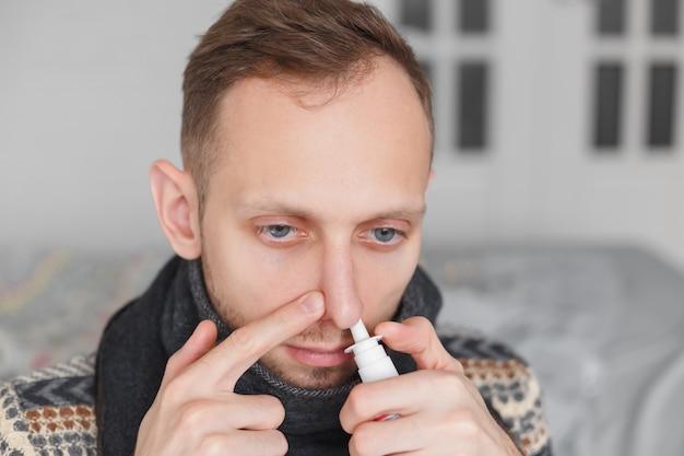 Człowiek za pomocą aerozolu do nosa.