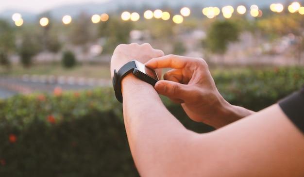 Człowiek za pomocą aplikacji smart watch. koncepcja mediów społecznościowych, biegacz na sobie smartwatch.