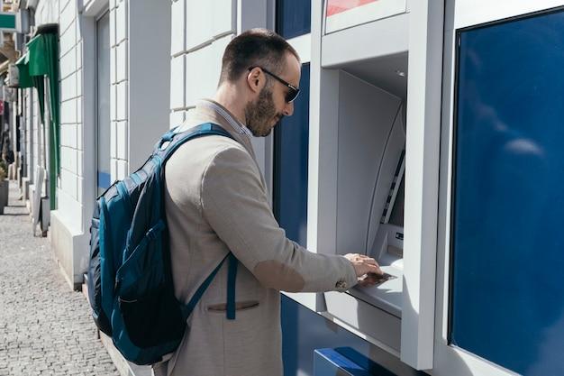 Człowiek za pomocą bankomatu