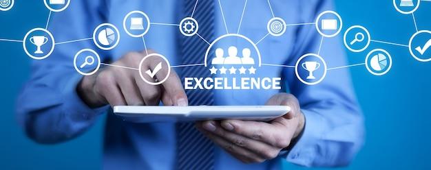 Człowiek za pomocą białego cyfrowego tabletu. doskonałość. jakość. biznes