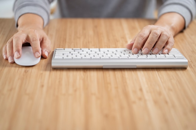 Człowiek za pomocą białej klawiatury komputerowej i myszy na drewnianym biurku.