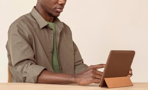 Człowiek za pomocą cyfrowego tabletu i siedząc przy swoim obszarze roboczym