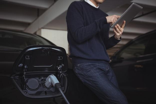 Człowiek za pomocą cyfrowego tabletu podczas ładowania samochodu elektrycznego
