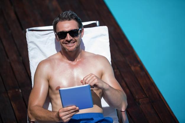 Człowiek za pomocą cyfrowego tabletu w pobliżu basenu