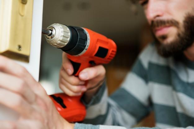 Człowiek za pomocą elektronicznej wiertarki zainstalować drzwi