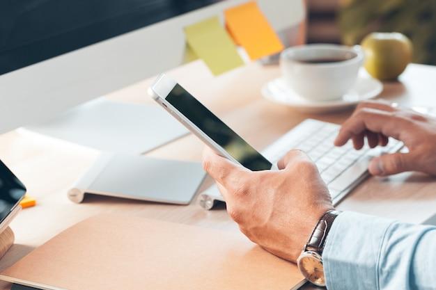 Człowiek za pomocą inteligentnego telefonu komórkowego. biznesowego mężczyzna ręki używać telefon komórkowego przy biurowym biurkiem.