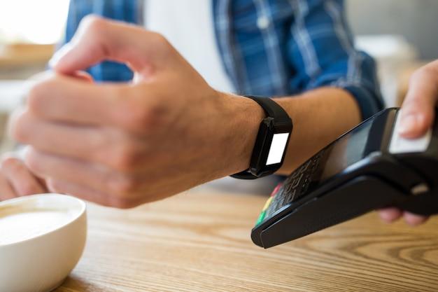 Człowiek za pomocą inteligentnego zegarka ekspresem wynagrodzenia