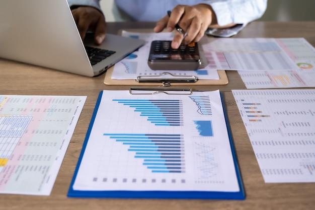 Człowiek za pomocą kalkulatora ze stosu pieniędzy raport finansowy-rachunkowość biznesowa koncepcja księgowania pieniędzy z wykresami statystycznymi