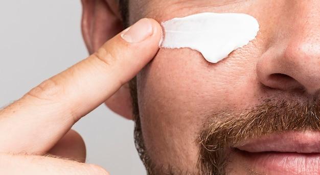 Człowiek za pomocą kremu do twarzy z bliska