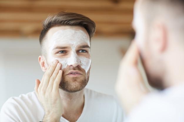 Człowiek za pomocą kremu do twarzy