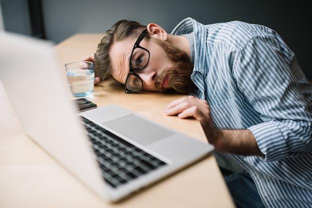 Człowiek za pomocą laptopa, czuje się zmęczony
