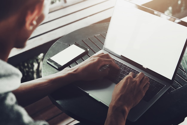 Człowiek za pomocą laptopa do pracy na linii w kawiarni
