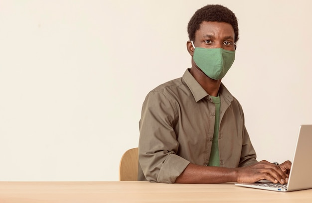 Człowiek za pomocą laptopa i noszenie zielonej maski medycznej
