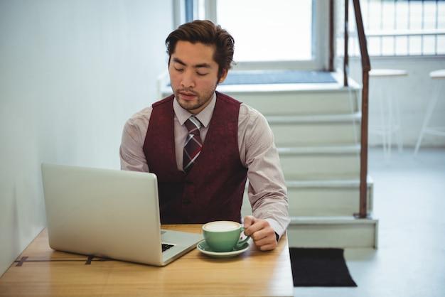 Człowiek za pomocą laptopa mając kawę