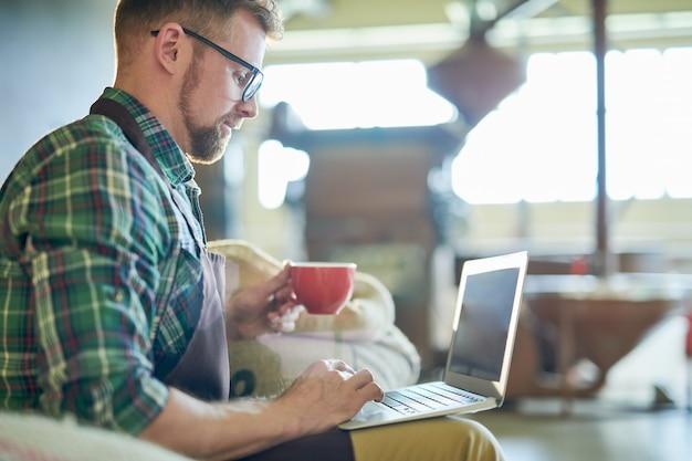 Człowiek za pomocą laptopa w palarni kawy