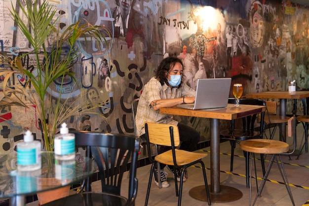 Człowiek za pomocą laptopa wewnątrz nowoczesnego baru.