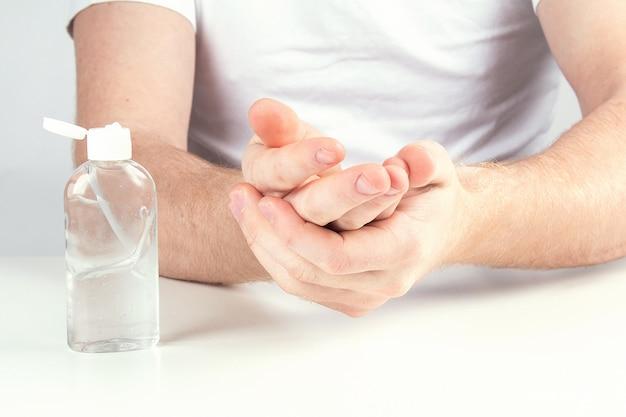Człowiek za pomocą małego przenośnego środka dezynfekującego rąk na ręce.