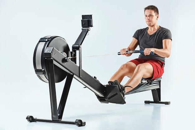 Człowiek za pomocą maszyny prasy w klubie fitness.