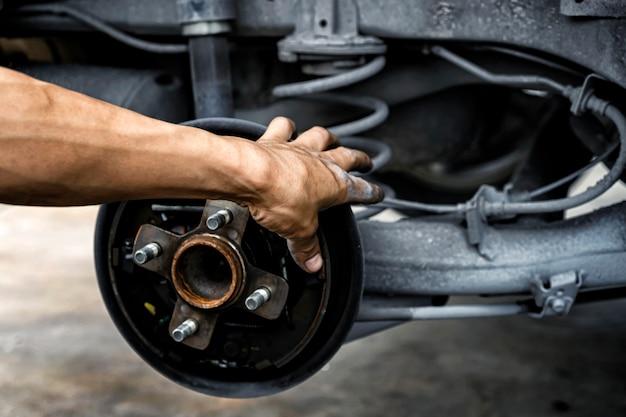 Człowiek za pomocą mechanika samochodowego zablokuj koło wiatru. sprawdzenie opon i hamulca samochodu. mechanik samochodowy przygotowanie do pracy.