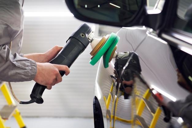 Człowiek za pomocą polerki do polerowania karoserii samochodu w warsztacie