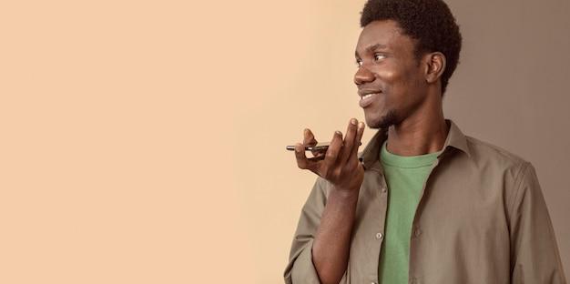 Człowiek za pomocą smartfona i rozmawiając na głośniku kopia przestrzeń