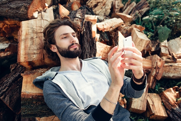 Człowiek za pomocą smartfona na stosie drewna.