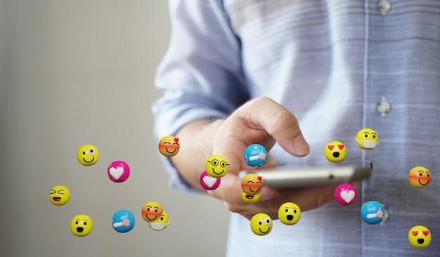 Człowiek za pomocą smartfona wysyłanie wiadomości tekstowych ikony emotikonów. koncepcja mediów społecznościowych, renderowanie 3d