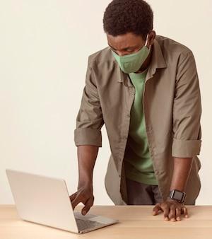 Człowiek za pomocą swojego laptopa i stojąc