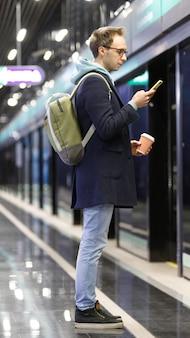 Człowiek za pomocą telefonu komórkowego, czekając na pociąg na stacji metra