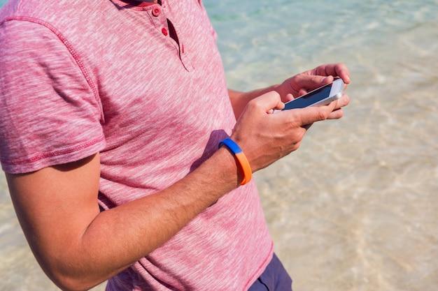 Człowiek za pomocą telefonu komórkowego na plaży