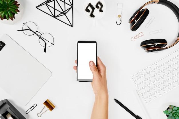 Człowiek za pomocą telefonu na makiecie kreatywnego obszaru roboczego
