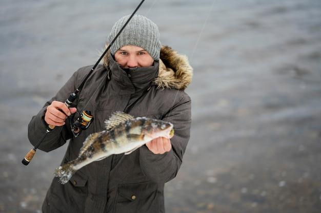 Człowiek za pomocą wędki do łowienia ryb