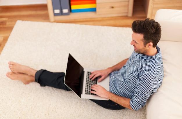 Człowiek za pomocą współczesnego laptopa w salonie