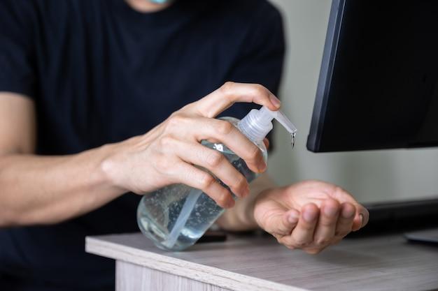 Człowiek za pomocą żelu do mycia rąk do ochrony koronawirusa podczas pracy w domu