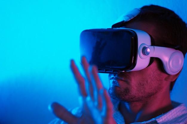 Człowiek za pomocą zestawu słuchawkowego vr w ciemne wnętrze oświetlone światłem neonowym. close-up futurystyczne gogle z kolorowym światłem. selektywne ustawianie ostrości.