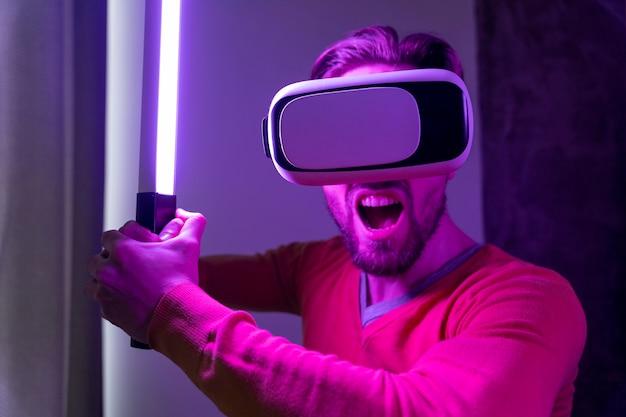 Człowiek za pomocą zestawu słuchawkowego wirtualnej rzeczywistości i grając mieczem laserowym