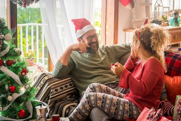 Człowiek zabawy z żoną picia kawy podczas obchodów bożego narodzenia w domu. kaukaska para śniadanie w przeddzień bożego narodzenia. para w salonie z dekorowaną choinką.
