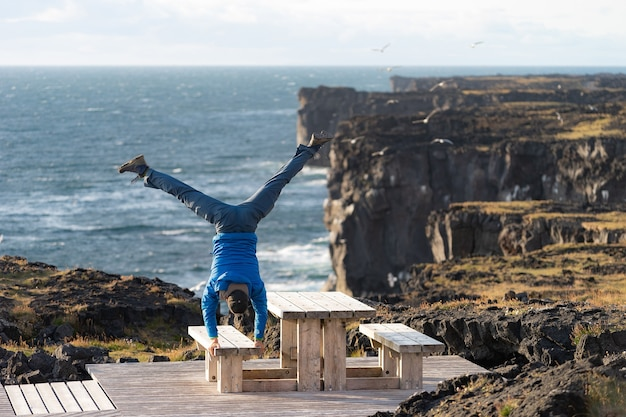Człowiek zachować równowagę stojąc na rękach na sea scape z niebezpiecznym tłem pionowego klifu, chmura podczas zachodu słońca